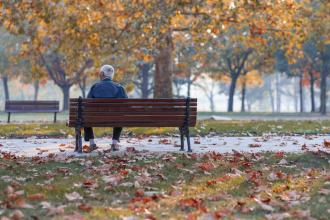 Lonely senior man sitting on a park bench