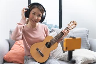 A girl plays a guitar while looking into a smart phone