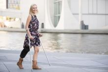 A woman walks with a knee brace and crutches
