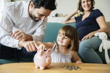 A couple sits with their small child with a piggy bank in front of them