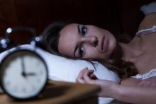 A woman lies awake in bed, staring at the clock