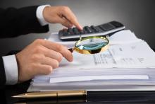 An auditor looks at invoices with a magnifying glass