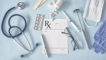 A selection of medical items: a stethoscope, pills, tongue depressors, glasses, gloves, and a face mask