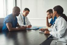 A group of doctors is sitting around a boardroom table and talking