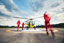 Three people in red suits are running to an air rescue helicopter