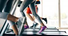 A group of people are running on treadmills at a gym