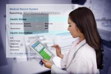 A doctor enters data in an electronic medical records system