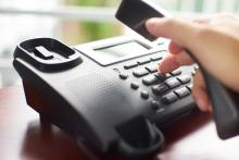A person dials an office-style phone