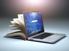 A laptop with an open book behind the screen, giving the idea of online learning