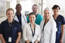 A multiracial group of smiling hospital staff in a hallway faces the camera.