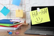 """A computer with a Post-it note that says """"haha"""""""