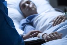 A terminally ill patient lies in a hospital bed, with her doctor by her side