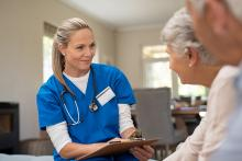 A home care nurse attends to a patient