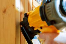 A construction worker uses a nail gun in close-up.