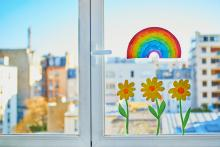A cheerful window with flowers and a rainbow painted on it