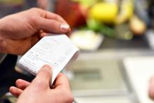 A pair of hands holding a receipt after payment in the supermarket