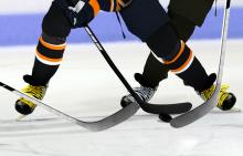 Ice hockey players face off on indoor rink