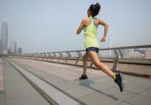 Female runner jogging with city and hazy sky in distance