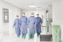 A team of doctors walks through the hospital wearing masks and gowns