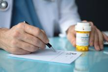 A doctor writes a prescription; a pill bottle is also seen beside the prescription paper