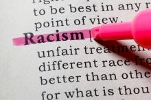 "A page from a dictionary with the word ""racism"" highlighted"