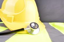 A hardhat and a stethoscope sit on top of a high-visibility vest