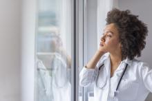 A young female doctor stands at a window, looking sad