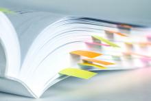 A book with colorful sticky notes marking various pages