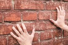 Hands pressed against a brick wall