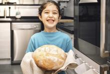 A young girl baking bread