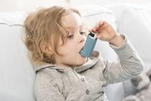 A young girl uses an inhaler