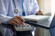A doctor does paperwork using a calculator