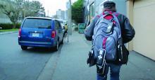 A man carries a backpack with Take Home Naloxone kits