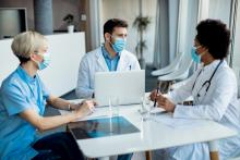 A team of doctors and administrators talk at a boardroom table