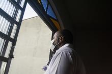 A doctor wearing a mask looks out a window