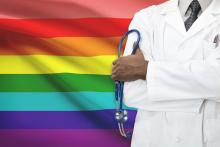 A doctor stands in front of a LGBTQ+ flag