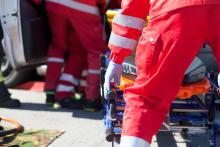 EMTs unload a stretcher from an ambulance