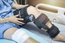 A patient sits on a hospital bed with a knee brace on
