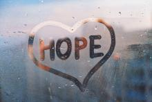 """A heart with the word """"Hope"""" in it has been drawn into condensation on a window"""