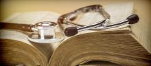 A stethoscope sits on top of an old medical textbook