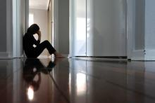 A teenager sits in a hallway, head down