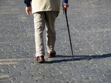A senior man walks with a cane