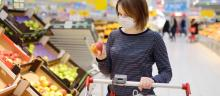 A woman shops for groceries with a mask on