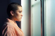 Young cancer patient looking out window