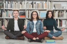 Multicultural students meditating with books on heads in library
