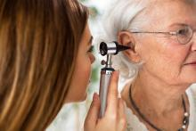 Doctor holding otoscope and examining ear of senior woman