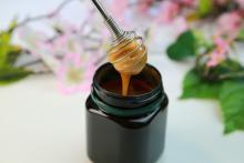 Manuka honey dripping into black jar blurred background