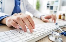 Doctor typing on a computer