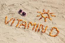 Sunglasses, inscription vitamin D and shape of sun on sand at beach, summer time and healthy lifestyle